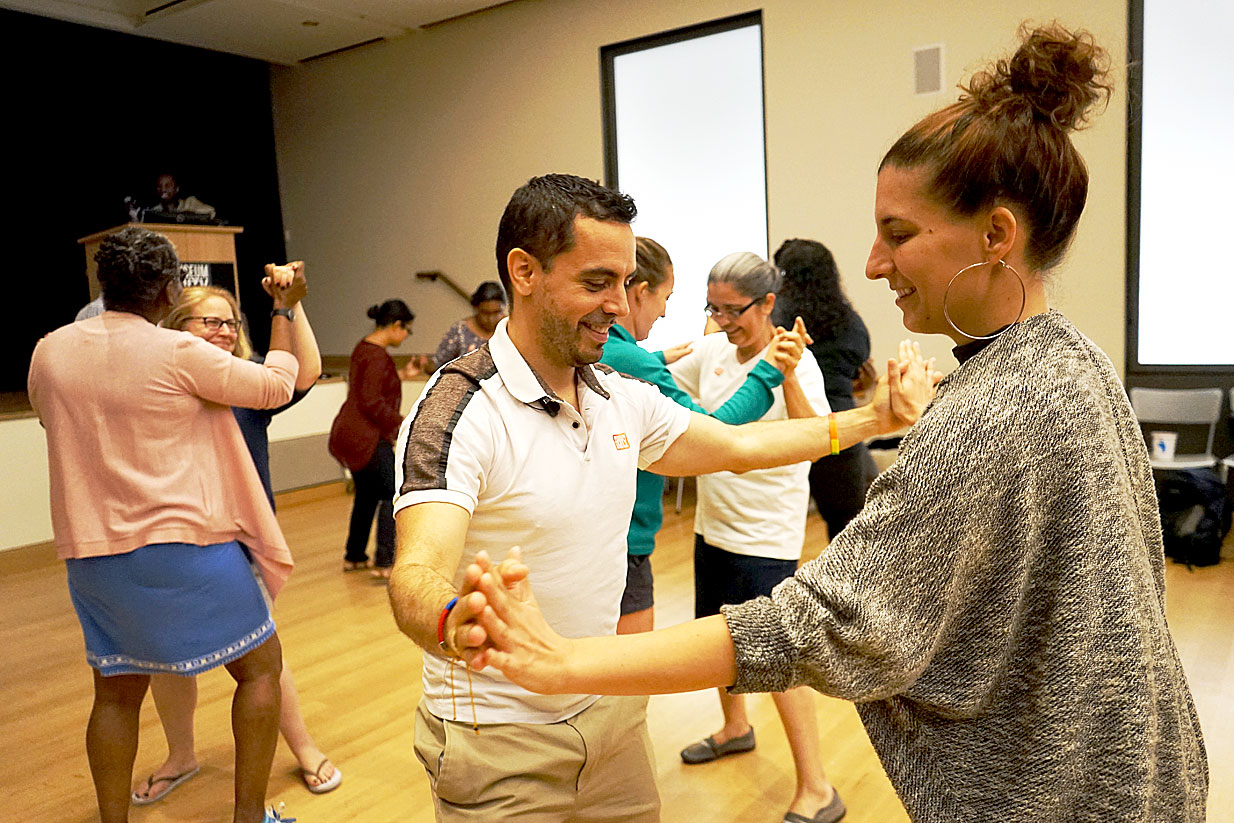 Educators, holding hands in pairs, taking part in a salsa dance lesson during the course.