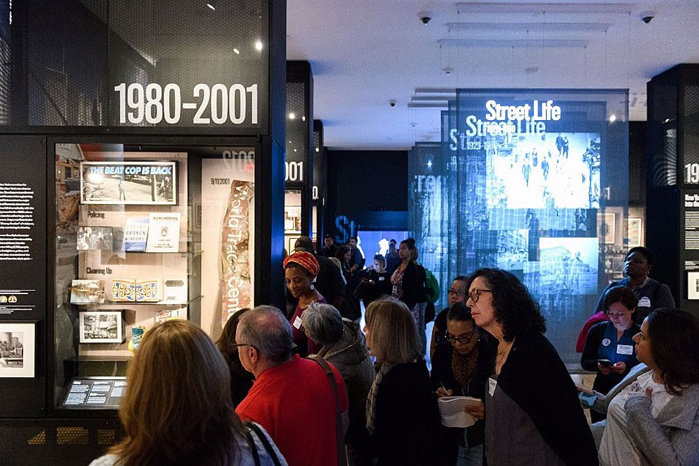 Educators listening to a tour in the New York at Its Core exhibition at the Museum of the City of New York.