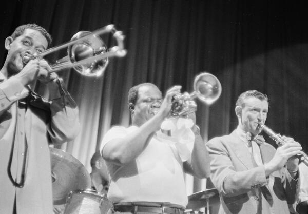 Photograph of Louis Armstrong playing the trumpet on the Jackie Gleason show alongside a clarinet player and a trombone player.
