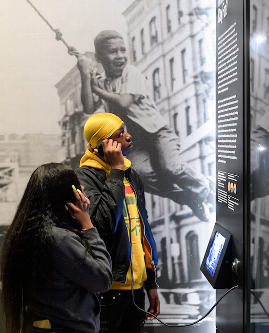 "Two students use headphones to listen to a recording in the ""World City"" gallery, part of ""New York at Its Core."""