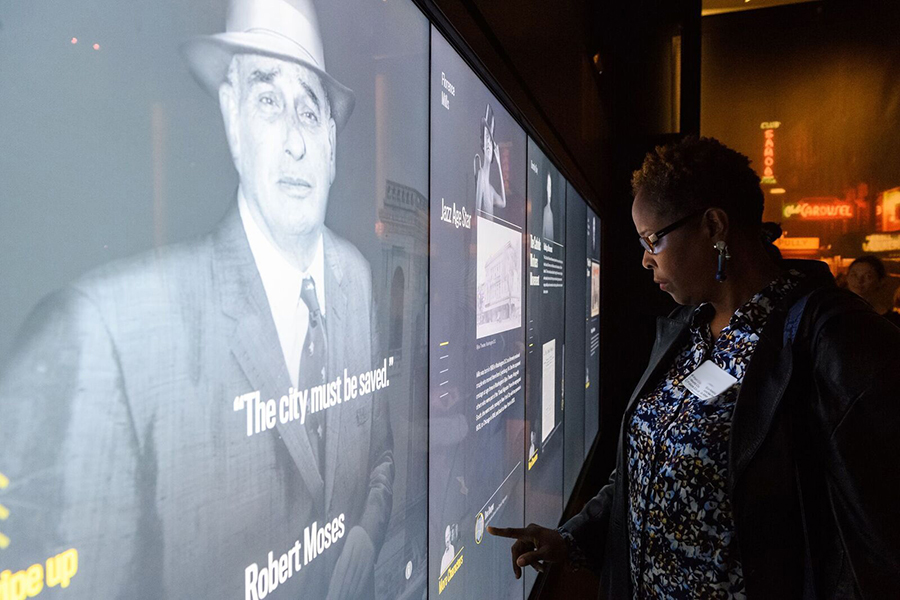 Um educador examina uma tela sensível ao toque que mostra as histórias de pessoas do passado de Nova York.