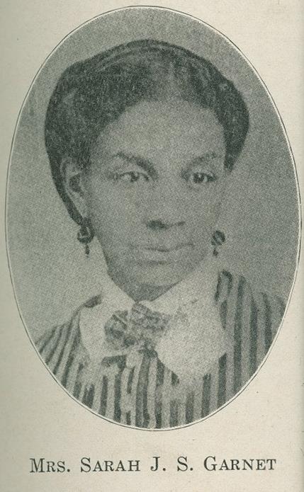 Uma fotografia de retrato formal em preto e branco de uma mulher negra usando um vestido listrado ou colete, colar de renda e fita e brincos.