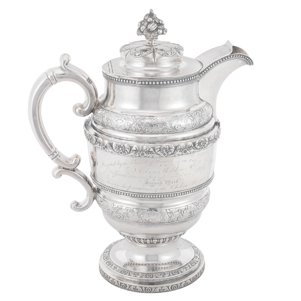 Silver pitcher with intricate details and writing in the middle