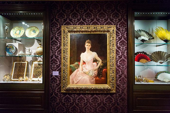 食器とファンを含むXNUMXつの展示ケース。 それらの間にあるのは、ピンクのドレスを着た座った女性の絵です