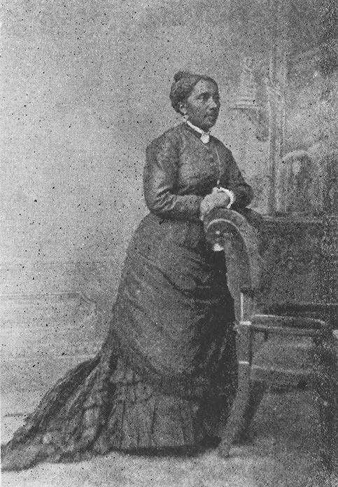 Um retrato de estúdio em preto e branco de corpo inteiro de uma mulher negra. Ela usa um vestido longo com saia, anquinha e renda, e um broche de pescoço e brincos.
