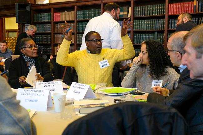 Un grupo de jueces del Día de la Historia se sienta a la mesa. Un hombre con un suéter amarillo tiene los brazos levantados, en medio de la discusión.