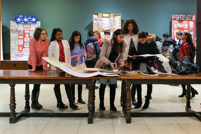 Un grupo de estudiantes se para a un lado de una larga mesa de madera mirando documentos y proyectos del Día de la Historia.