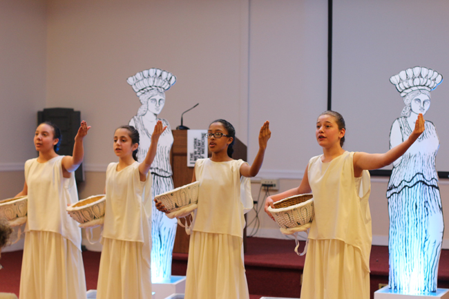 Cuatro chicas vestidas con traje griego se paran frente a dos cariátides hechas a mano. De rendimiento medio, se paran con un brazo extendido y el otro sosteniendo una canasta.
