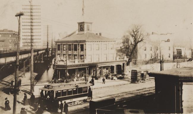 Photographie d'une intersection avec une ligne de tramway au niveau de la rue et une plateforme surélevée au-dessus.