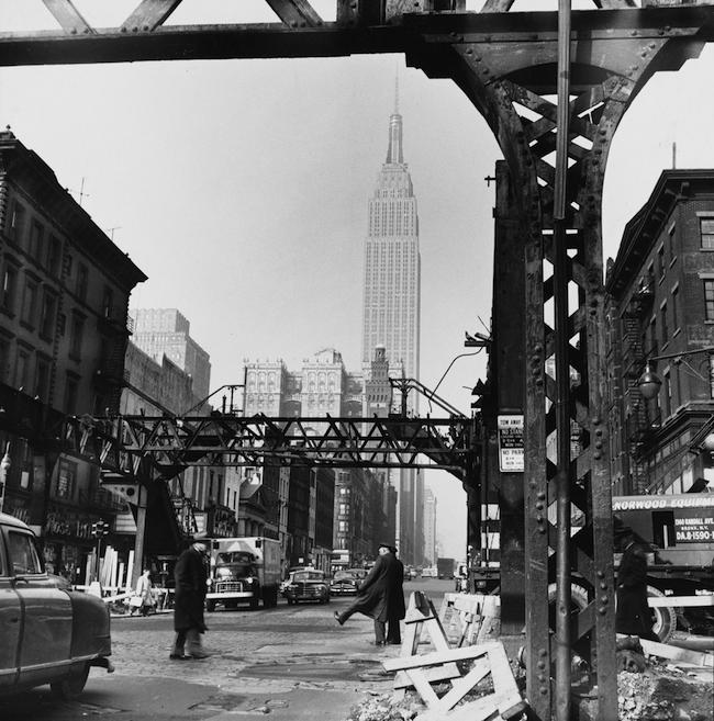 Photographie de voies ferrées surélevées partiellement démontées avec l'Empire State Building en arrière-plan.