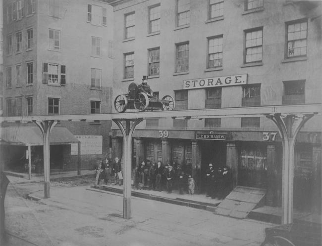 Photo en noir et blanc d'un homme monté sur un chariot sur une plate-forme surélevée au-dessus d'une rue de la ville.