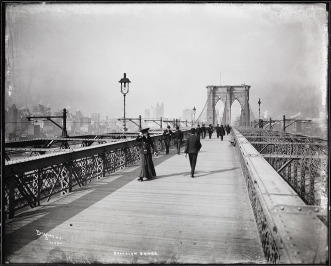A black and white photograph of people walking along the Brooklyn Bridge in 1903