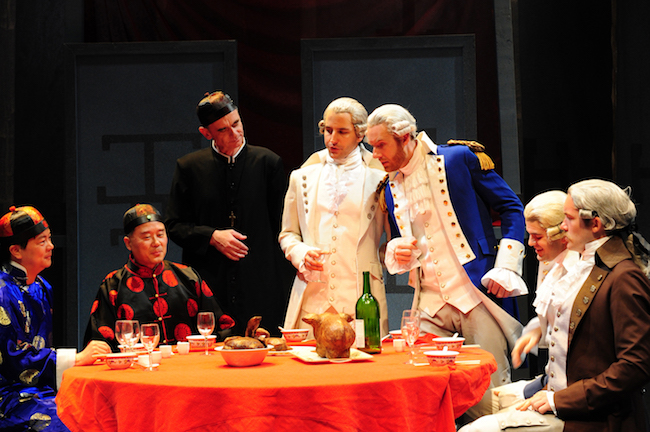 A color photograph of a group of seven costumed actors gathered around a table. Three on the left (two seated and one standing) wear traditional Chinese clothes, while the remaining men (two standing, two sitting) where powdered wigs and colonial dress.
