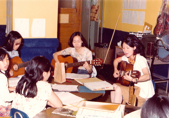 Photograph of a group of women sitting around a table in a classroom-like setting, all holding guitars with papers in front of them.