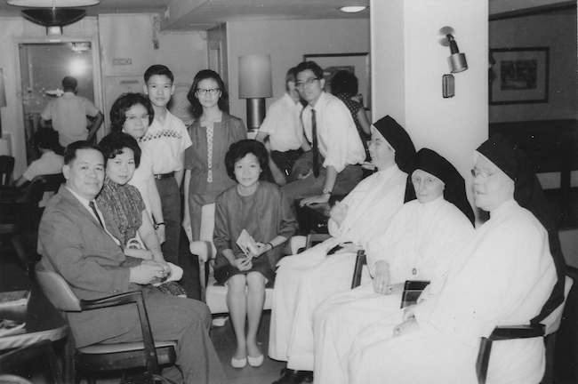 Black and white photo of an asian family sitting with a group of nuns.