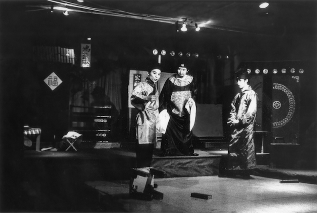 "A black and white theater still from ""The Tale of the Romanic Fan."" Three actors in traditional Chinese costume stand apart, one on the left turning towards the auidence."
