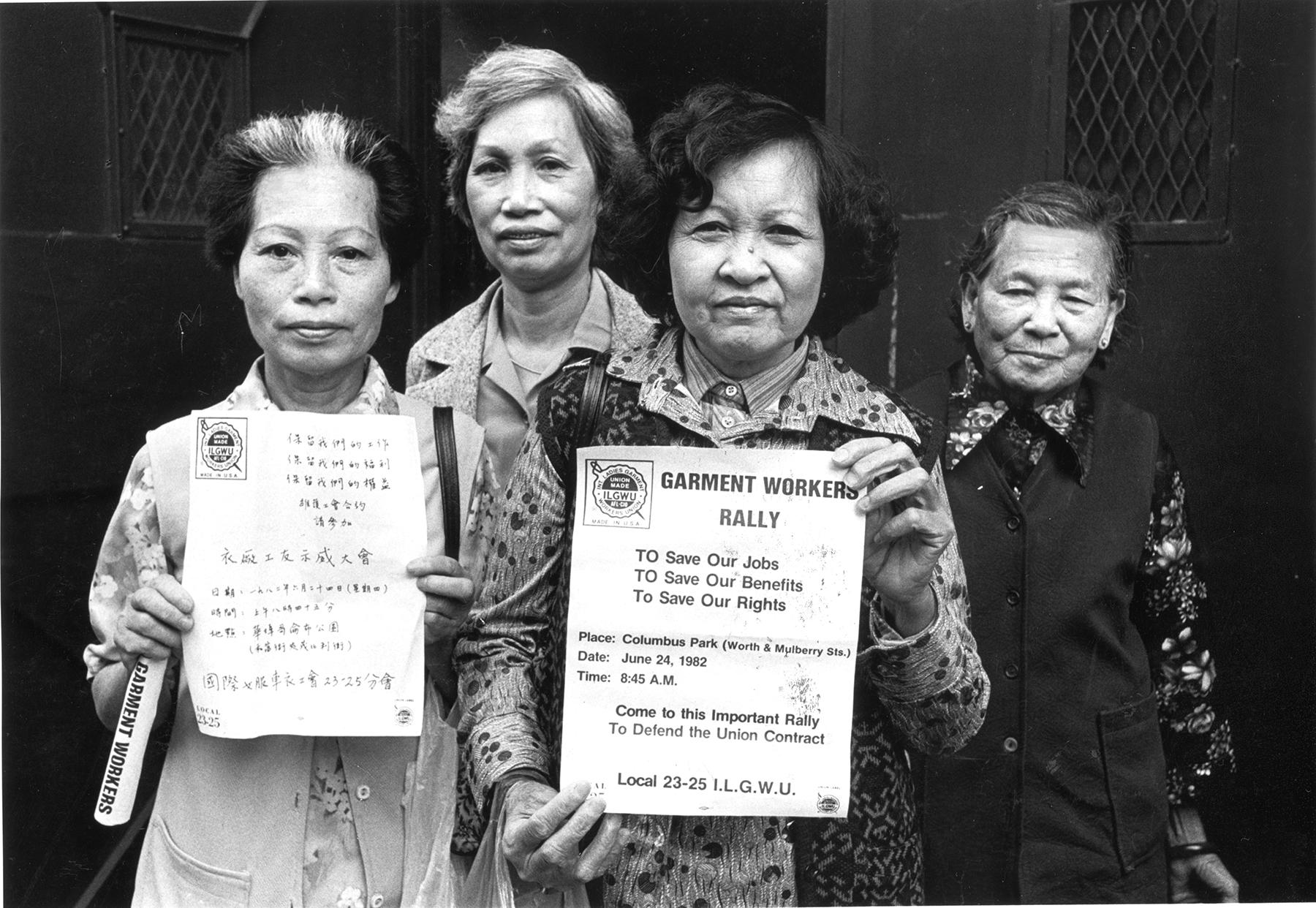 Membros do sindicato ILGWU Local 23-25 olham diretamente para a câmera e exibem panfletos em inglês e chinês em apoio à greve contra as fábricas de roupas em Chinatown, na cidade de Nova York.
