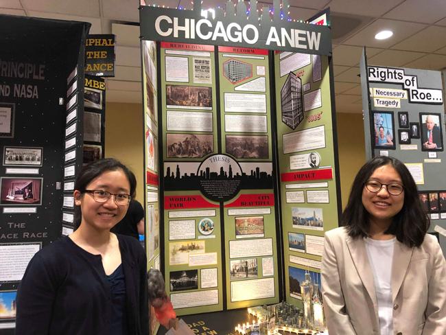 """Dos estudiantes se paran a ambos lados de su proyecto del Día de la Historia, un panel de exhibición que se centró en """"La tragedia del gran incendio y el triunfo de la ciudad de los rascacielos"""""""
