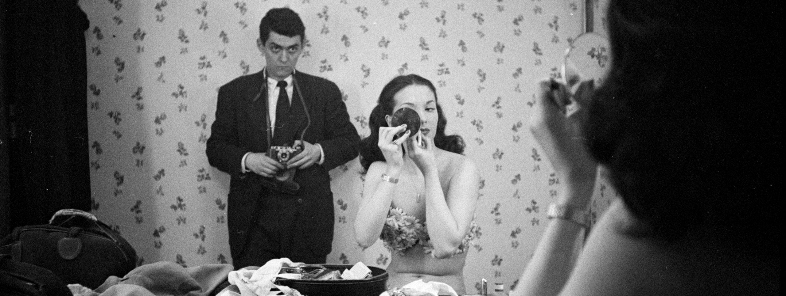 Tomada no reflexo de um espelho, uma mulher usa um espelho compacto para aplicar maquiagem, enquanto o fotógrafo fica atrás dela assistindo