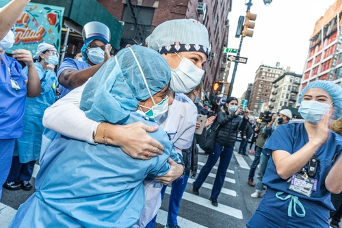 Color photograph of two women in full scrubs and protective gear hugging on a NYC street with other individuals, also in scrubs, surrounding them.