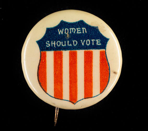 "Women's Suffrage button that says ""Women Should Vote"" with an image of shield with the red, white, and blue coloring of the American flag."