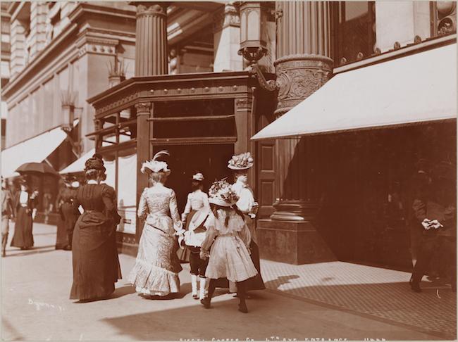 デパートの前を歩いている19世紀のドレスを着た女性のグループの写真。