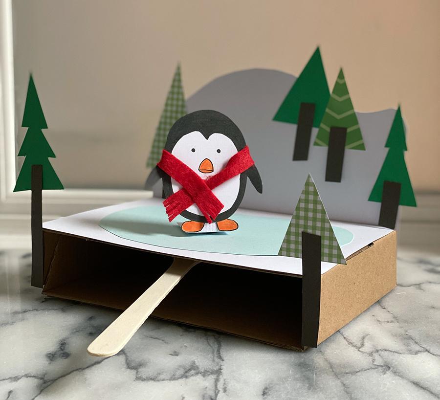 Uma foto de um projeto artesanal usando papel e papelão para criar um pinguim com um lenço patinando em um campo de gelo congelado.
