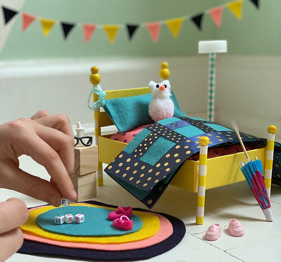 Uma fotografia de um conjunto colorido de mobília de quarto em miniatura, incluindo uma cama com bichinho de pelúcia, mesa de cabeceira, tapete e decorações. A mão de um adulto segurando um minúsculo bloco está entrando na visão pela esquerda, como se fosse colocá-lo no tapete.