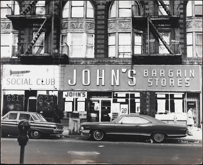 "Street view of Myrtle Avenue, Bed-Stuy, close-up of shop fronts ""John's Bargain Stores"" and ""Social Club"" with cars from ca. 1970 parked in front."