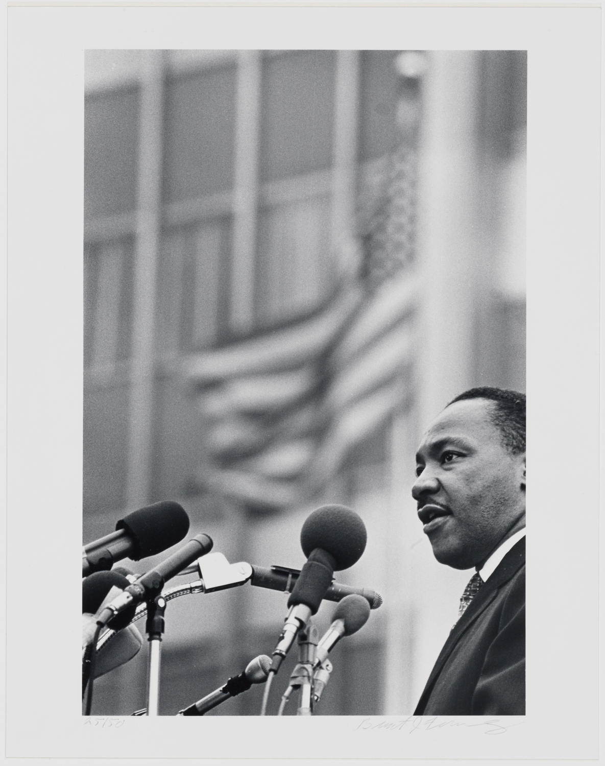 Black and white photograph of Martin Luthur King Jr. standing at a microphone with a building and flag waving behind him.