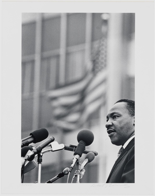 彼の後ろに建物と旗を振ってマイクに立っているマーティンルーサーキングジュニアの白黒写真。