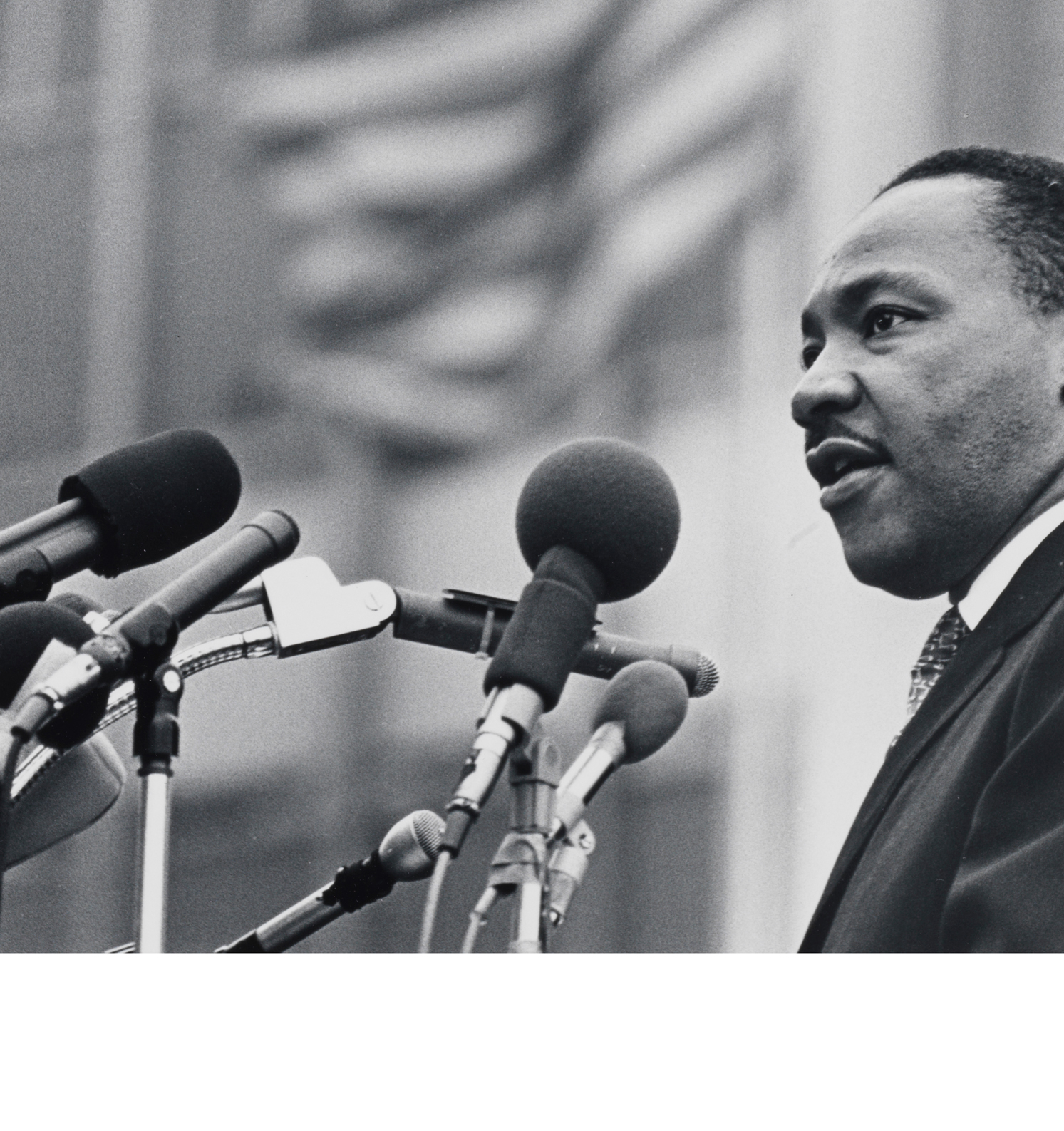 Image of Dr. Martin Luther King Jr. speaking into several microphones.