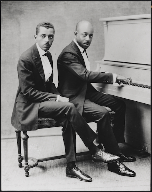 Two African-American gentlemen in suits sit on a piano bench, with a piano to the right. The man on the right has his hands on the keyboard.