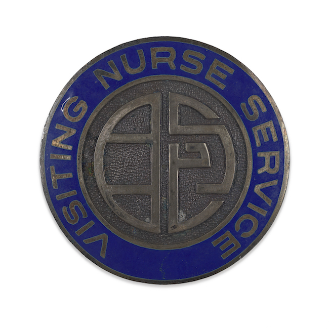 "Metal lapel pin. An abstract design in plain metal in the center is surrounding by a blue enamel ring with the words ""Visiting Nurse Services"""