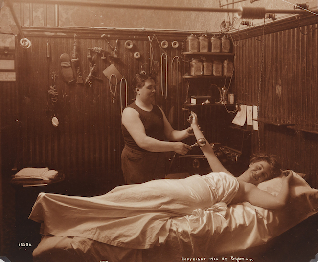 A woman reposing, receiving some sort of massage therapy in a Turkish bath.