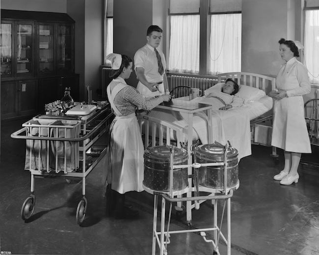 A black and white photograph of three nurses standing around a patient in a hospital bed.
