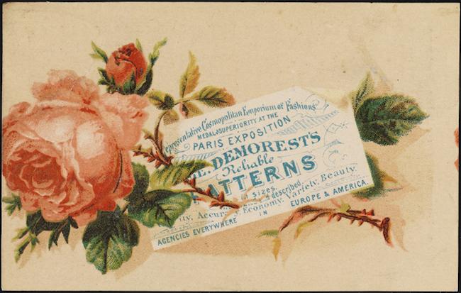 画像の横に表示されている、満開のピンクのバラの上に小さなつぼみがあり、葉と棘のある茎に取り付けられています。 小さな白いカードが青いテキストで茎の上に置かれます。