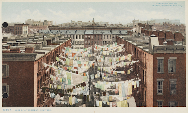 A color postcards showing rows of clotheslines with laundry hanging off them between two rows of apartment buildings.