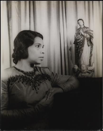Retrato en blanco y negro de Marian Anderson frente a una cortina. Sus brazos descansan sobre una superficie oscura, con una estatua de una figura religiosa junto a su codo izquierdo.