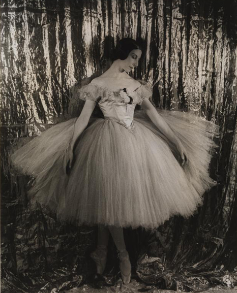 A portrait of a ballerina, in costume, standing en pointe in front of a curtain.