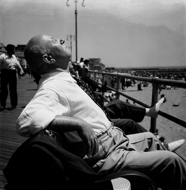 Black and white photo of a man relaxing on a bench on the boardwalk