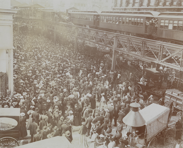 Crowds of people outside Siegel Cooper department store on its opening day in 1896, with the Sixth Avenue elevated train above.