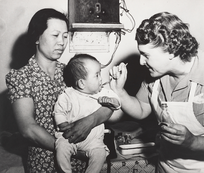 Black and white photograph of a nurse spoon-feeding an Asian-American baby, held by his mother.