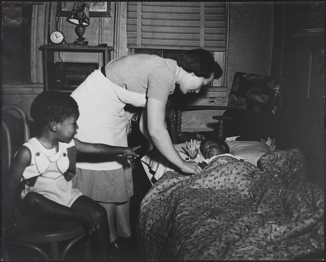 A nurse tucks a small child into bed, while another, seated in a chair, looks on.