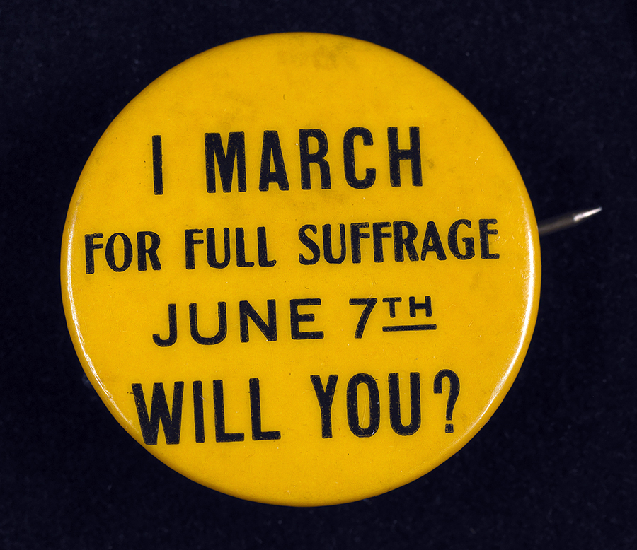 A small gold button supporting voting rights for women from the early 20th century reads: I March for Full Suffrage June 7th. Will You?