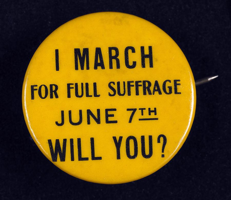 Un petit bouton en or soutenant le droit de vote des femmes du début du 20e siècle se lit comme suit: Je marche pour le suffrage complet le 7 juin. Vas-tu?