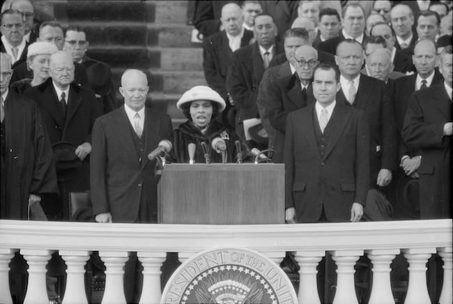 A fotografia mostra a cantora Marian Anderson se apresentando na posse de Eisenhower, com o presidente Eisenhower e o vice-presidente Richard Nixon por trás dela.