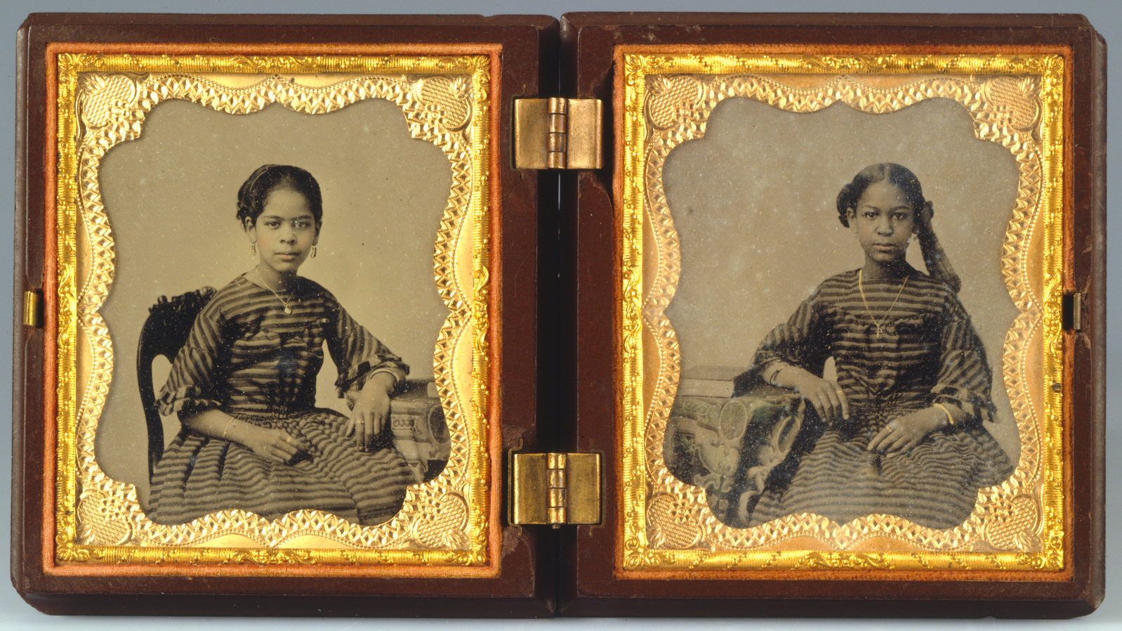 Duas fotografias em preto e branco de cada lado de uma caixa de madeira com dobradiças e ouro mostram duas meninas negras usando vestidos em tecidos e joias combinando.