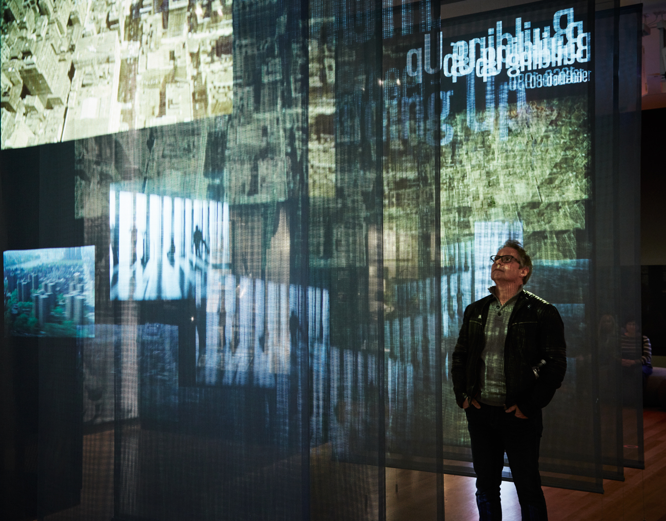 A visitor stands in-between sheer panels as a video projection plays across them