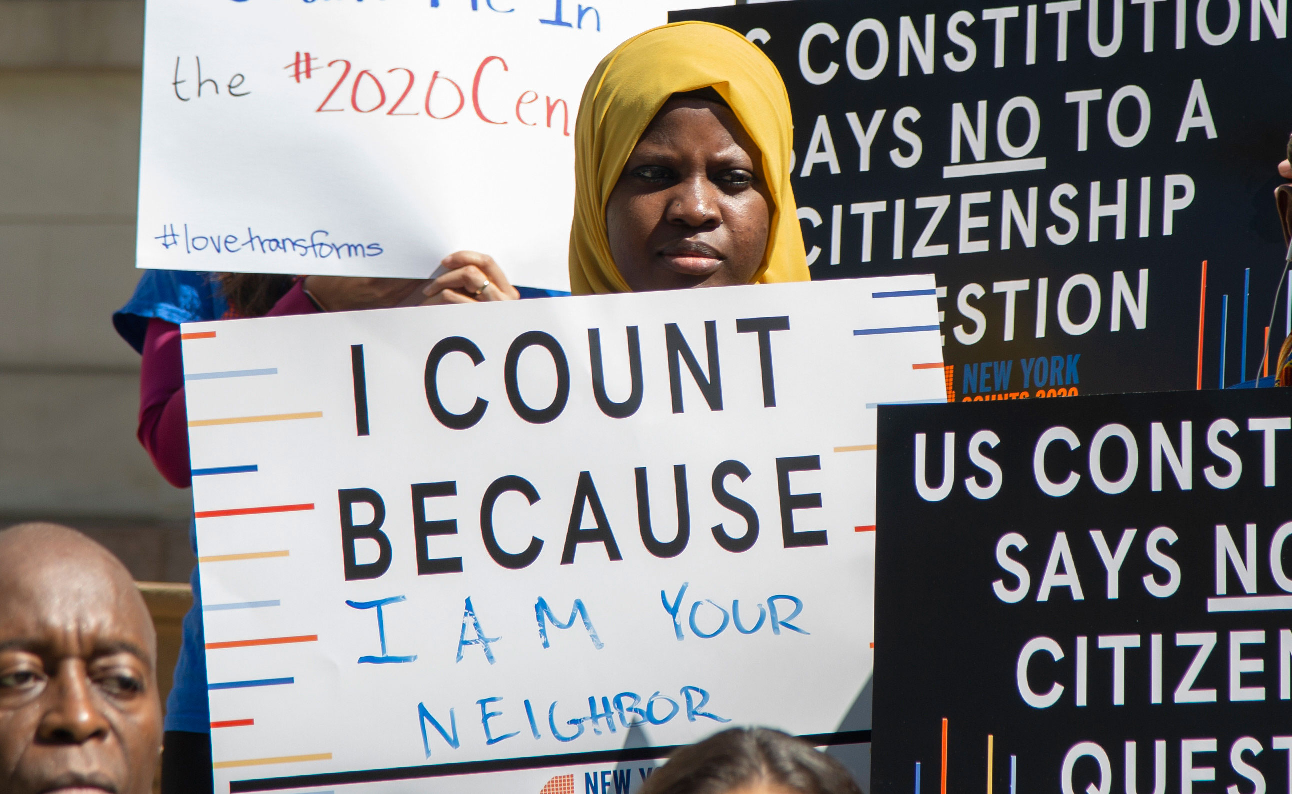 "Image shows a young person at a New York City Council press conference holding a sign reading ""I Count Because I Am Your Neighbor."""